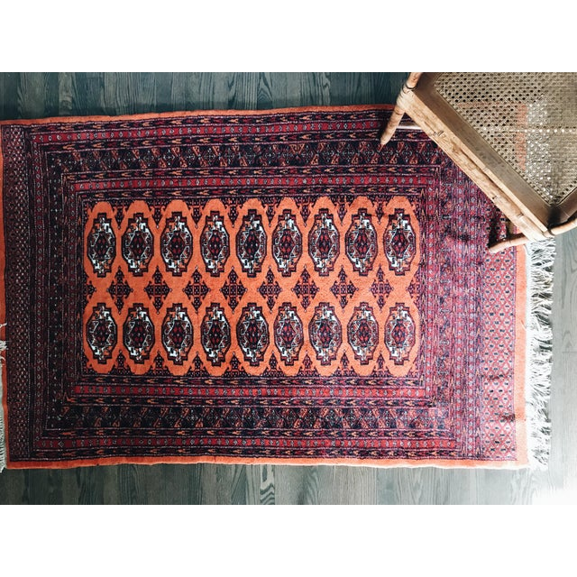 A semi-antique, Hand-Knotted Wool Rug. Features geometric designs on a rectangular field in a palette primarily of orange,...