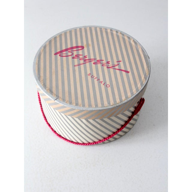 This is a vintage Berger's hat box circa 1950s. The chic hat box features a white and silver stripes with rose pink cable...