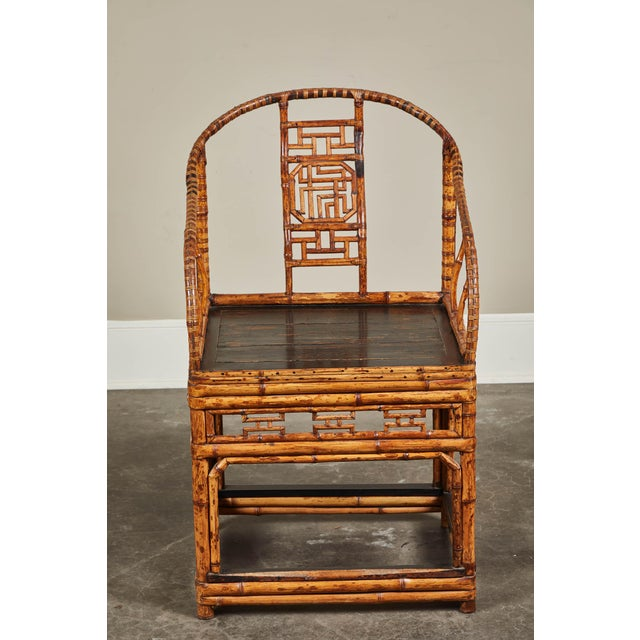 A 19th century Chinese horseshoe back armchair. Made from sturdy bamboo with a black lacquered seat and back splat details.