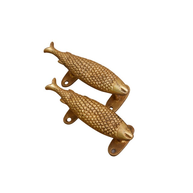 A pair of brass fish door handles or cabinet pulls. Hollywood Regency in style, with intricate carving throughout....