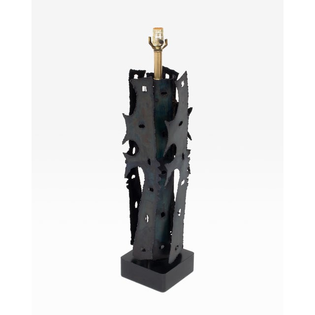 Here is an impressive brutalist style mid century table lamp. Features torch-cut/welded panels and wooden base....