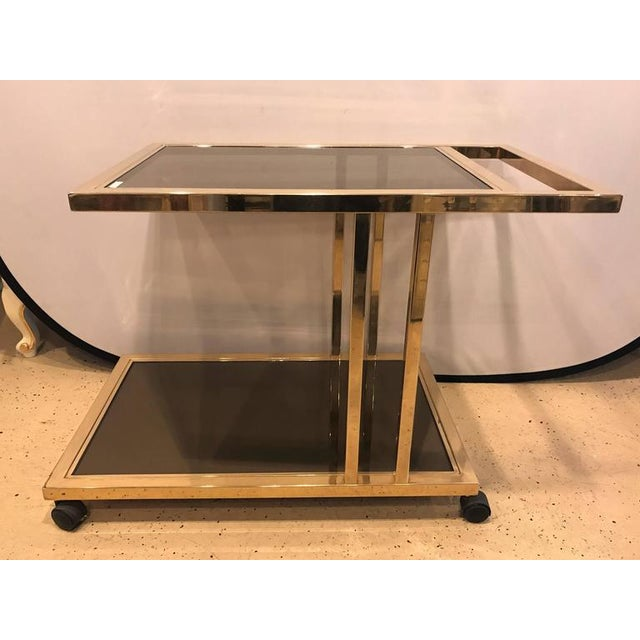 Italian brass and smoked glass bar cart. The whole on rolling casters leading to a lower bottom shelf of smoked glass...