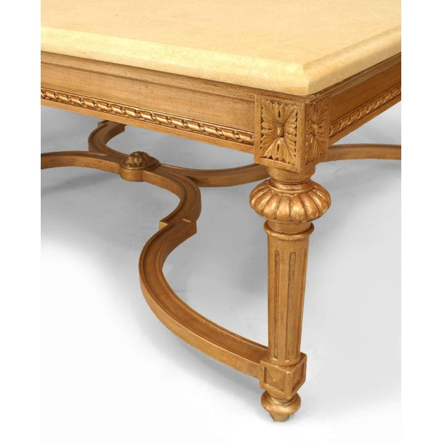 20th century French Louis XVI style large gilt rectangular coffee table with a shaped stretcher and beige marble top.