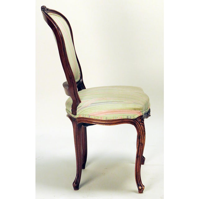 This is a French chair with carved details to top rail and seat, having cabriolet legs.
