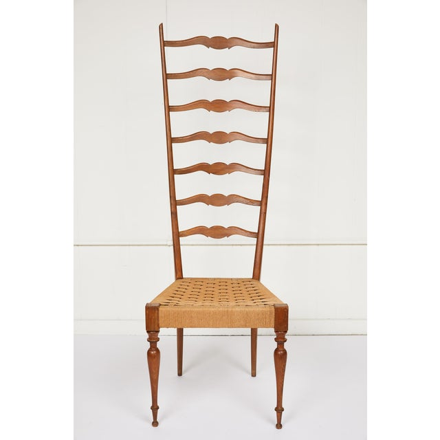 20th century elegantly formed chair made in the region of Chiavari, Italy. The chair's tall stylized ladderback terminates...