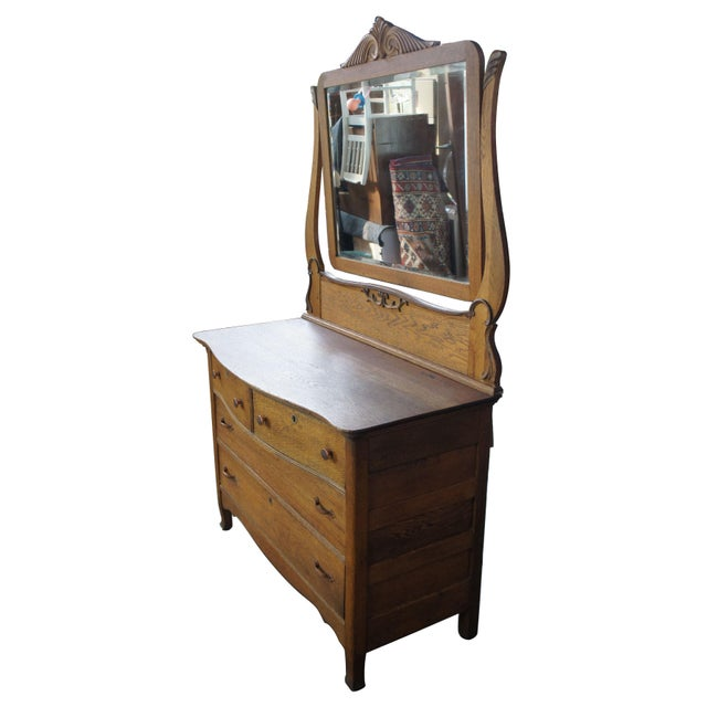 Turn of the century late Victorian dresser with carved wishbone mirror. Made from oak with a serpentine front, paneled...