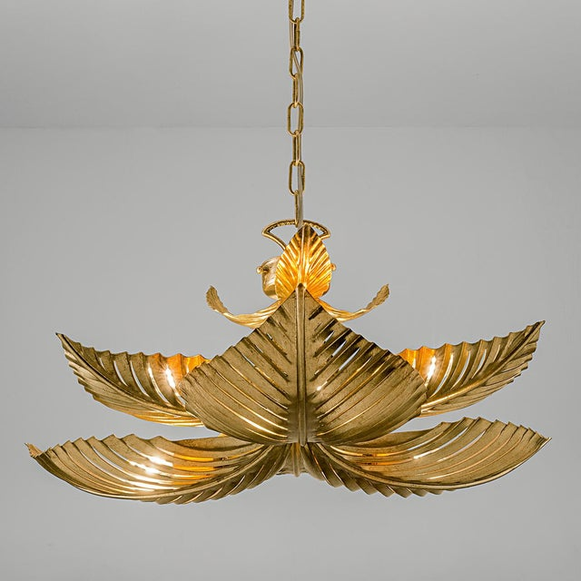 Hand made and decorated metal palm leaves pendant light in Florentine antique gold leaf which allows light to emit through...