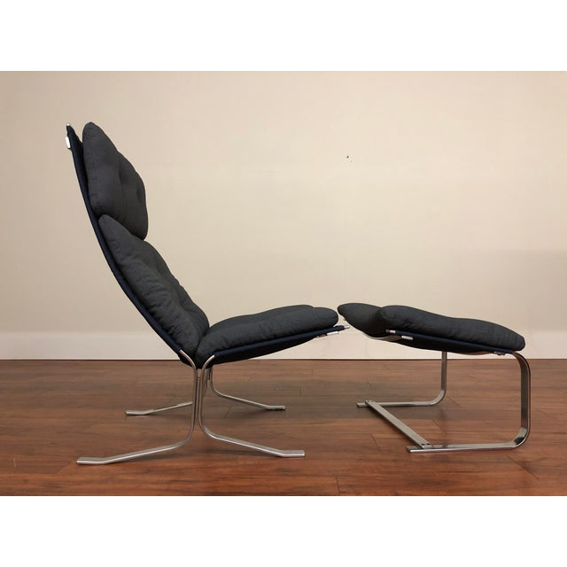 High back vintage lounge chair with matching ottoman made in Denmark by S. Lund. Chair and ottoman have a metal frame,...