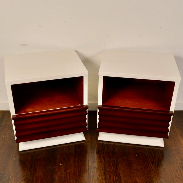Nice sculptural front mahogany nightstands from the 50s that have been updated with a white lacquer. Each piece features a...