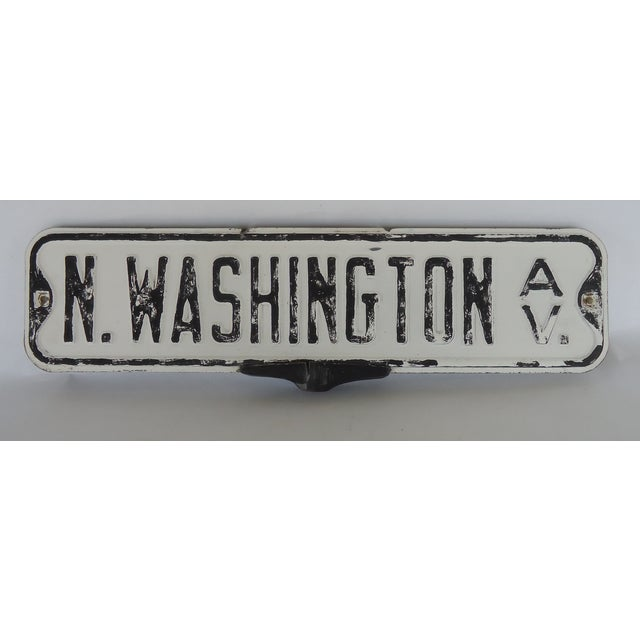 A vintage street sign, N Washington Avenue, consists of two signs (one for each side) on a metal holder. Has moderate wear...
