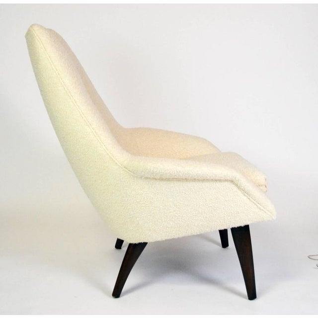 """A sculptural Danish lounge chair with a loose seat cushion and tufted back, on curved, tapered walnut legs. Arm height 20""""..."""