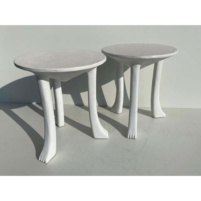 """Pair of African tribal side tables in the style of John Dickinson made of carved wood covered with plaster. 22.5"""" round by..."""