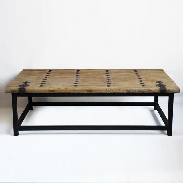 An old elm wood solid coffee table with iron details and a simple black iron base.