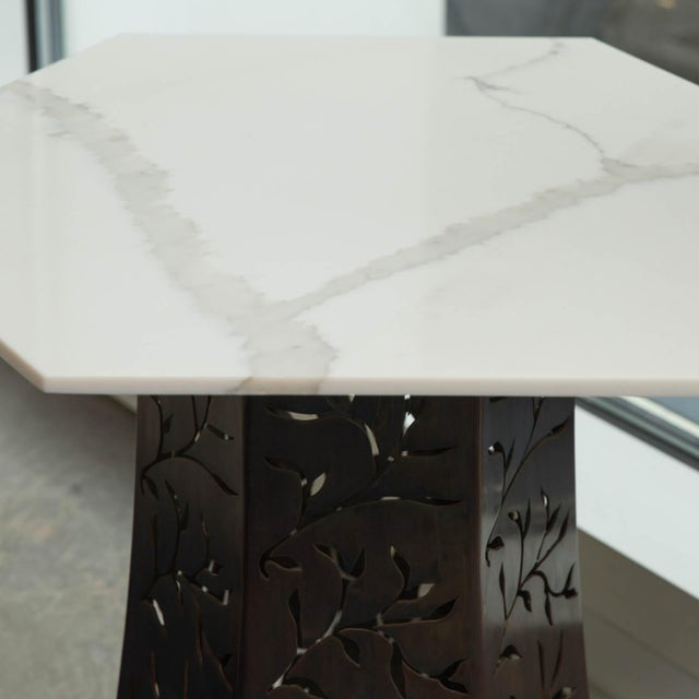 Hexagon shaped Carrara marble-top on a patinated steel base, with a custom filigree pattern.