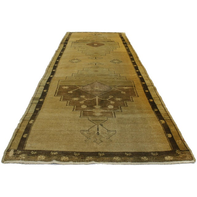 Vintage hand-knotted wool Turkish Oushak runner with double center medallion in an open abrashed field.
