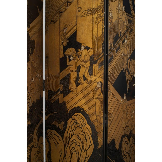 Twentieth century decorative screen in the Chinese manner. This twelve panel, black lacquered screen features an incised...
