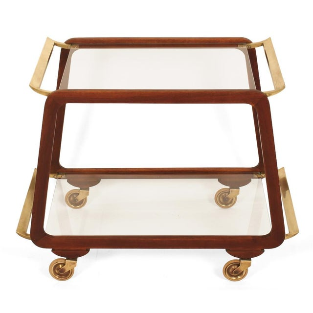 A beautiful serving trolley comprising a pair of walnut silhouette frames with solid brass wing handles and removable...