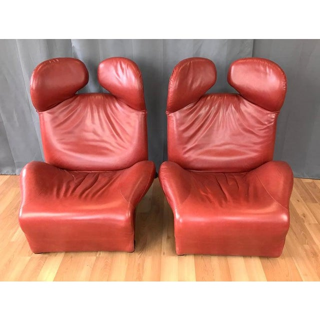 An early 1980s pair of sensuous cranberry red leather Wink lounge chairs by Toshiyuki Kita for Cassina. Ingeniously...