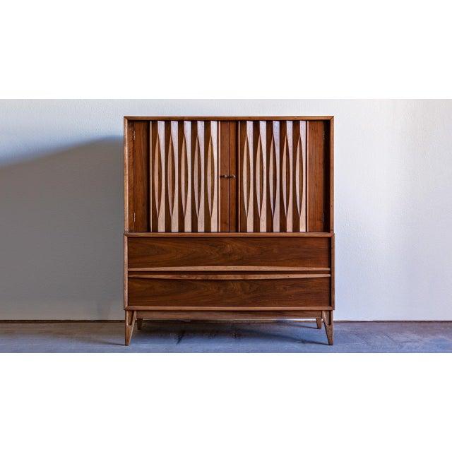 Mid-century modern walnut highboy dresser manufactured by Thomasville Furniture Co. Features beautiful walnut wood grain,...