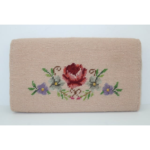 Accessorize an ensemble with this sweet floral needlepoint clutch handbag in shades of putty pink, green, yellow, brown,...