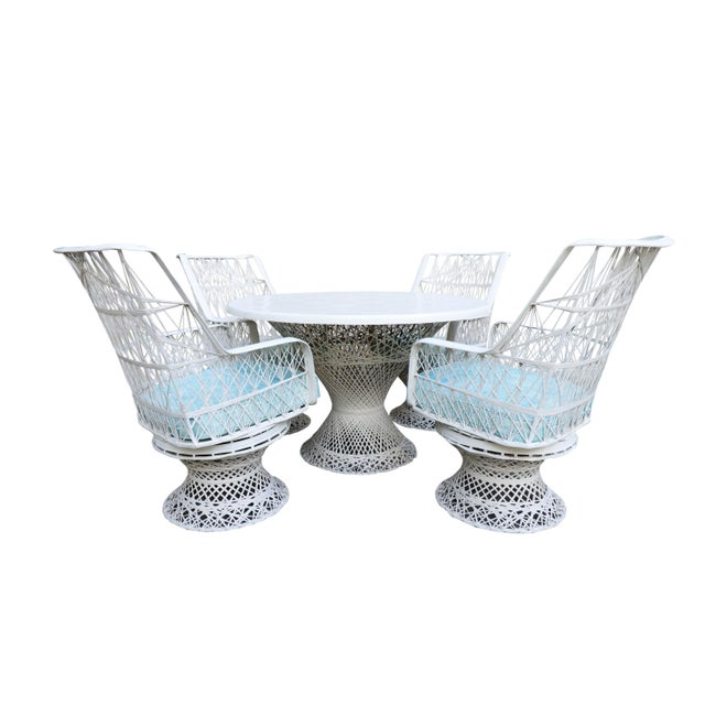 A mid century modern spun fiberglass patio dining set, designed by Russell Woodard. Four chairs and a pedestal table are...