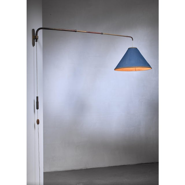 A brass, swiveling, height-adjustable and extendable wall lamp by Gino Sarfatti. The lamp has a telescope arm and a...