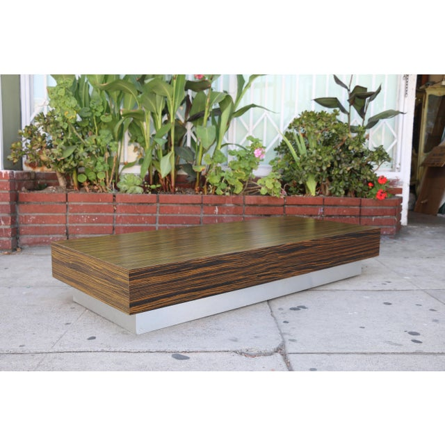 New custom made coffee table in good condition. Zebra wood style top with aluminum base.