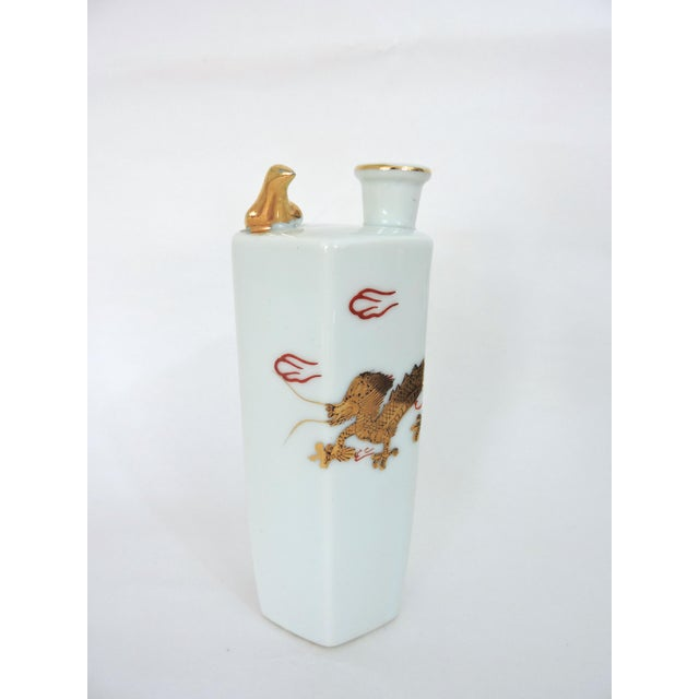 Fine white porcelain Japanese sake flask highlighted with gold leaf decorations and a dove that whistles and chirps...