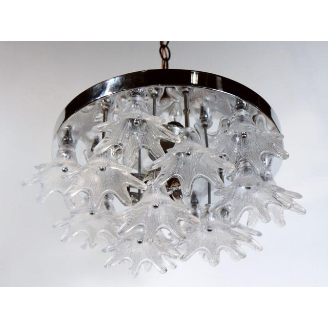 A plafonnier with a circular chrome canopy holding a 'cluster' of molded glass flowers. American, circa 1960s.
