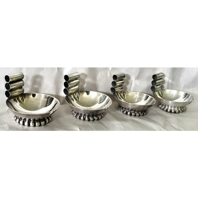 Beautifully designed individual ashtrays fashioned in silver plate with three holders for cigarettes and a circular beaded...