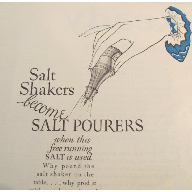 "About The Poster: An elegant blue and white advertisement page for Morton's Salt company, ""When it rains - it pours plain..."