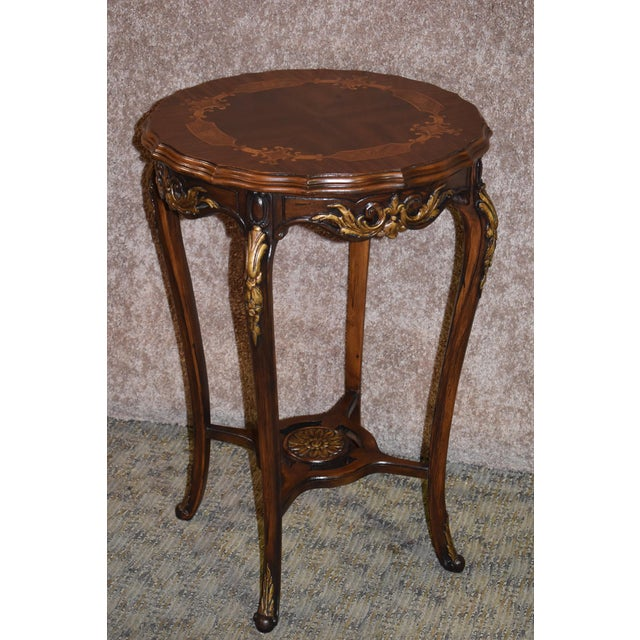 Antique French style accent table is made of wood. The top is made of exotic inlaid woods. The color is a warm brown...
