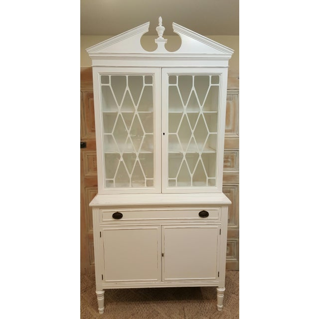 This is a vintage china cabinet painted white and distressed. Original hardware. This is one solid piece this does not...
