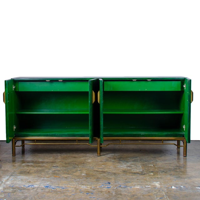 An impressive Italian faux malachite lacquered sideboard with chinoiserie inspired brass base and handles. Made in Italy...
