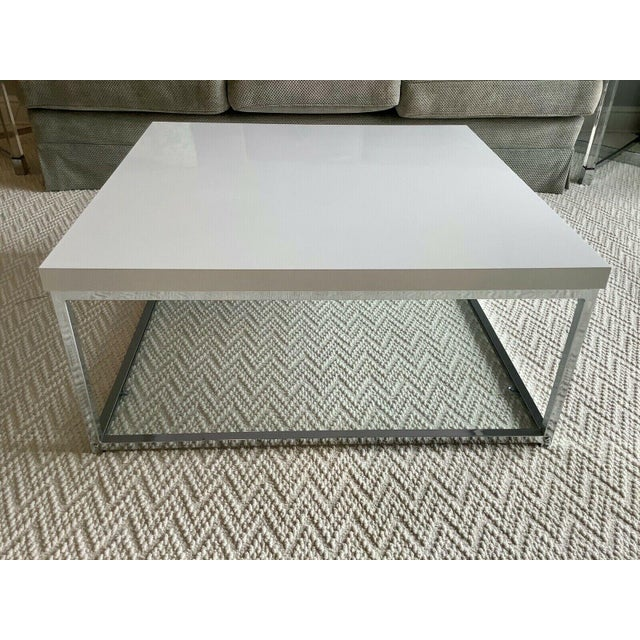 The clean lines of this modern coffee table are finished in a high gloss white lacquer, chrome frame and a tempered glass...