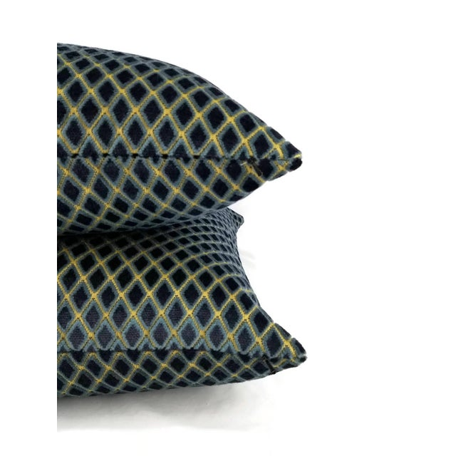 A deep royal blue or others call navy diamond pattern velvet pillow cover. In between the diamond lines are a goldish...