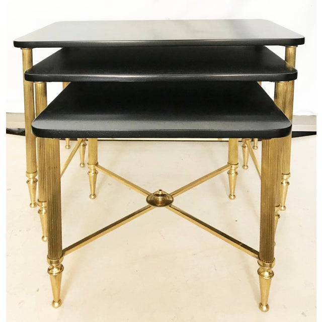 Set of three bronze and black ebonized nesting table, by Maison Jansen Size: Large : 21 inches L, 13 inches W, 18 inches H...