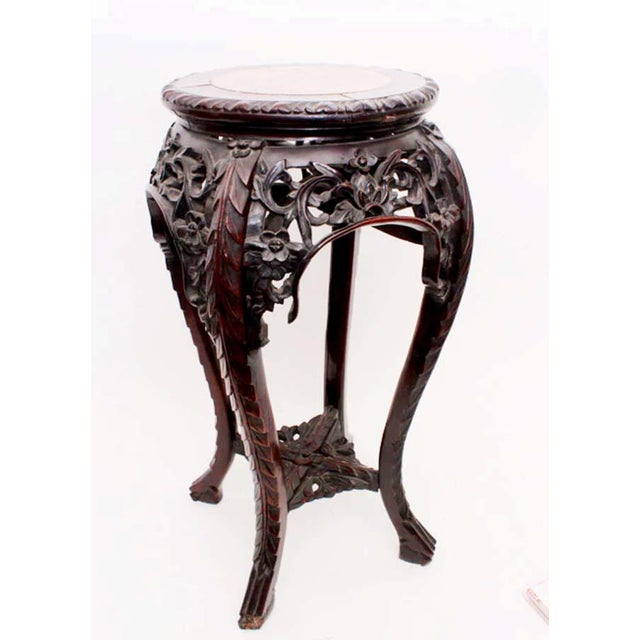 Antique Chinese carved rosewood plant stand Marble inset and framed top Carved border above an ornately carved apron and...