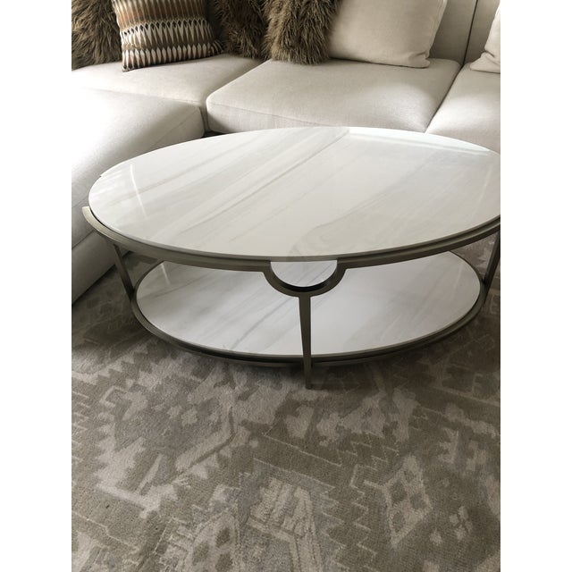 Glamorous sophisticated modern oval two tier coffee table having white faux marble surfaces and clean grey steel...