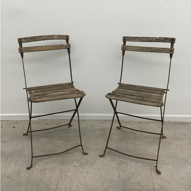 A pair of Vintage French garden chairs with original finish. Metal legs and base with wooden slats. Slats are in overall...