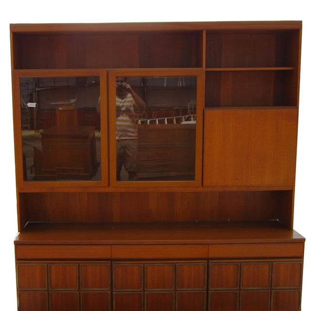 Vintage Mid Century teak credenza with a display cabinet from Europe. The display cabinet has a drop-down, leather-inset...