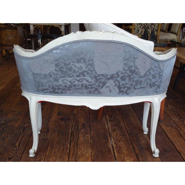 Very pretty little loveseat with painted and gilded carved wood, newly redone in a platinum colored tone on tone fancy...