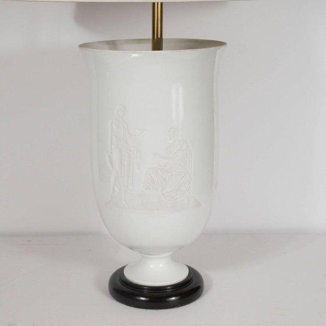 This refined Art Deco table lamp was realized from white glass in an urn form. It depicts two Greco Roman figures in...