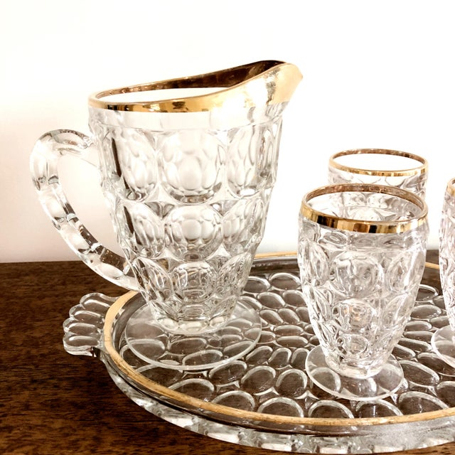 """Antique 1920s presses glass cocktail set. Includes: gold-rimmed tray, 3 glasses, 1 pitcher. Tray: 13"""" x 8"""" x 3/4"""" Pitcher:..."""