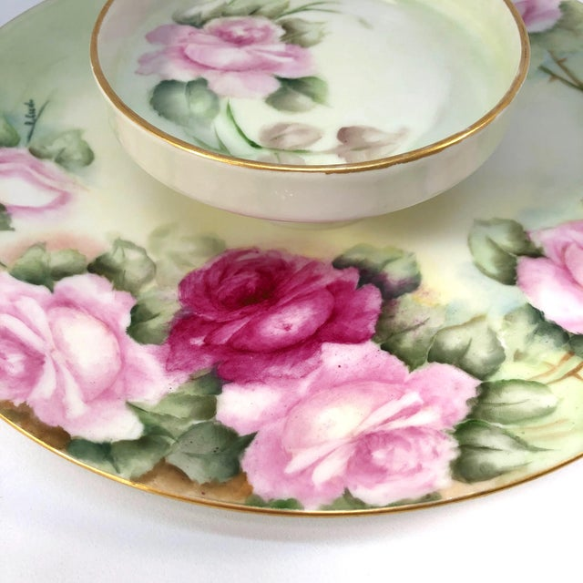 A tiered porcelain serving dish by Limoges, presented in pale green with a rosette motif and gold tone trim. The piece is...