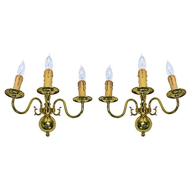 Pair of midcentury Dutch-style three-arm brass sconces. Newly polished and wired. Each sconce uses three chandelier bulbs.
