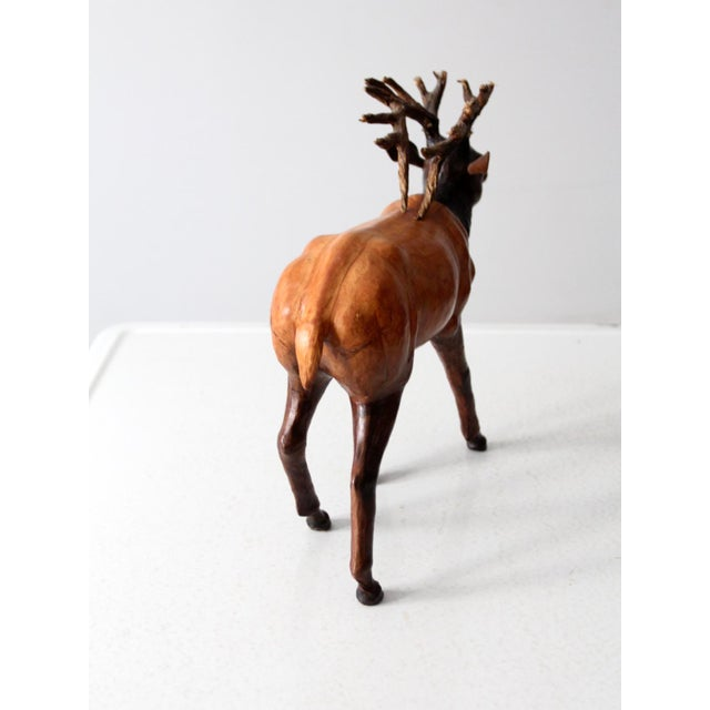 This is a vintage leather reindeer sculpture. Beautifully toned leather shapes the animal with glass eyes and wooden antlers.