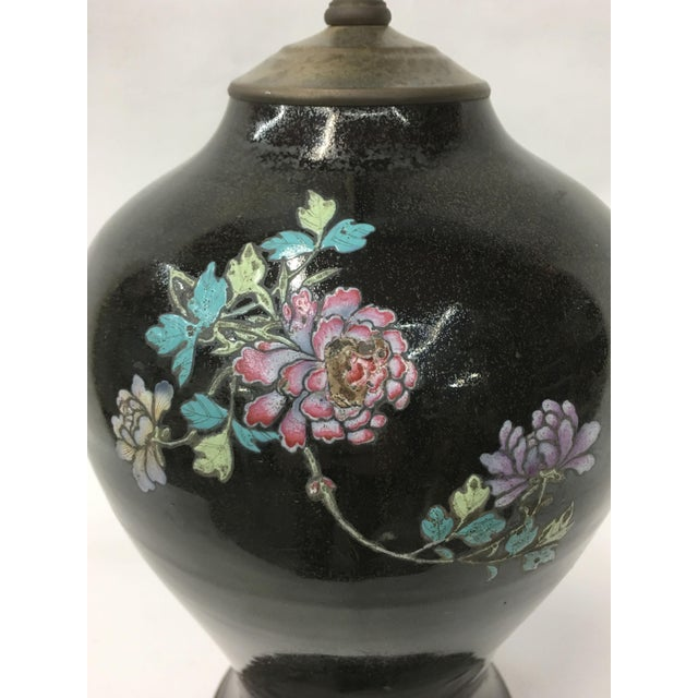 This deep black vintage lamp features delicate scattered flower motifs and makes an excellent feature to any home.