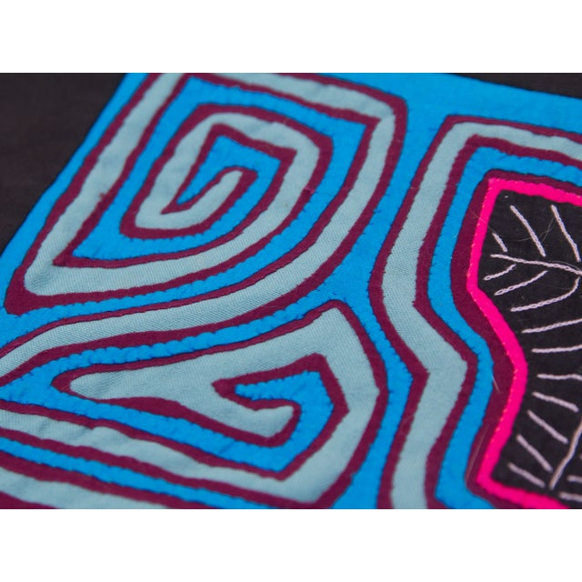 A black cotton pillowcase featuring an authentic Panamanian mola (textile sewn in the traditional reverse stitching...