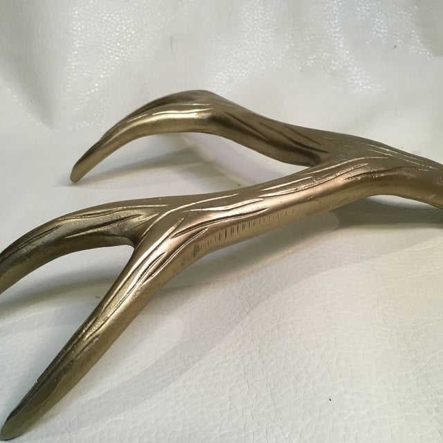 Brass color Aluminum Antler. Now that's a Paperweight!I love it on a stack of books on a coffee table.